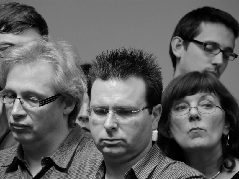 De ontgoocheling druipt van de gezichten tijdens de redactievergadering. Dit zijn de mensen die níét ontslagen zijn. Langzaam dringt het besef door dat zij weleens de grootste slachtoffers van de herstructurering zouden kunnen zijn.