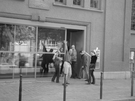 Enkele personeelsleden van De Morgen die het lezersprotest even hebben bijgewoond, keren terug naar binnen voor hoofdredacteur Bart Van Doorne hen een voor een weer achter hun bureau sleurt.