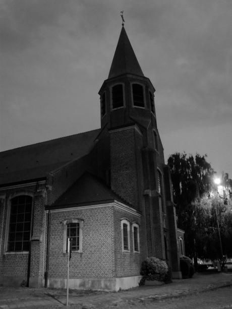 De kerk van Oostakker bij nacht. Eenzame pelgrims vinden het onverwachte geluk als zij onder haar toren staan.