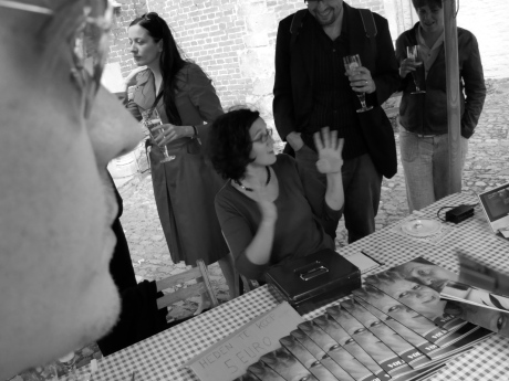 Teun Van de Voorde verkoopt exemplaren van 'Achter de gevels. Volkscafés in Gent', waaraan ze zelf meeschreef. Links in beeld zien we het gelaat van lay-outer Steve Reynders.