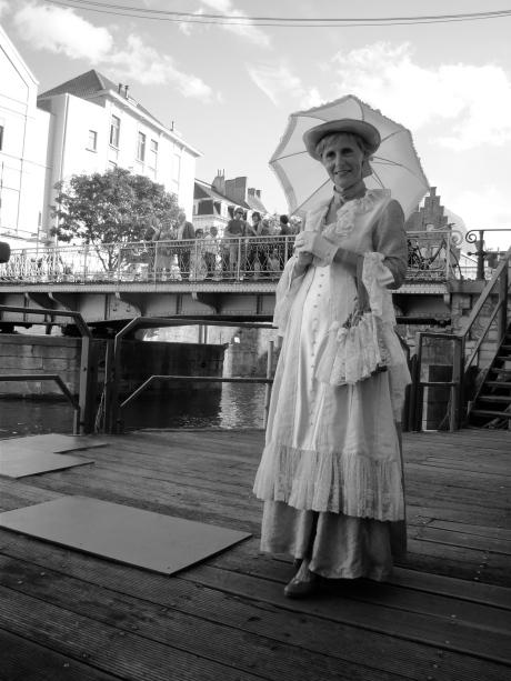 Een dame heeft zich uiterst stijlvol aangekleed voor de Feesten. Helaas zal ze met zo'n outfit niet veel kunnen uitrichten op de Vlasmarkt.