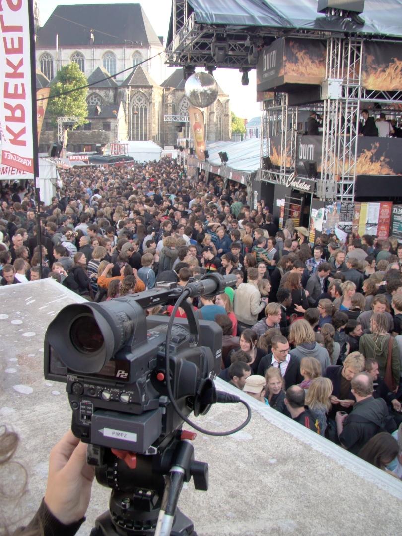 De Vlasmarkt om iets voor acht uur 's morgens, gezien van op het dak van de wc-cabine. Het volk is nog massaal aanwezig en wordt lustig gefilmd door cameralui van Hans Buyse.