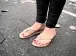 Een meisje poseert met haar tenen. Ze maakt zich zorgen over haar vuile voetjes, maar op dit moment van dag en op deze plaats valt dat best mee.