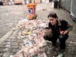 Een vrouw met een leren broek fotografeert het afval van de Vlasmarkt.