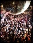 De discobal van Damocles hangt de bezoekers boven het hoofd. Hun lot is feesten of sterven.