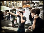 Twee jonge gasten laten hun vrienden weten dat ze zich keihard staan te amuseren op de Vlasmarkt.