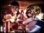 Jill controleert of er geen nieuwe klanten zijn terwijl Nicolas en Chrissie elkaar innig omhelzen.