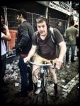 Een fietser met hoog opgetrokken kousen baant zich een weg tussen het nafeestende volk.