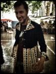 Een man is blij dat hij zijn kleed aangetrokken heeft. Zo kan hij de regen beter trotseren.
