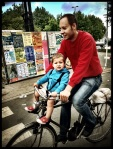 Parcifal fietst zijn zoontje Kazimir rond op de Vlasmarkt. Het ventje trekt een zeer bedenkelijke blik.
