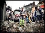 Stoïcijns blazen de kuismannen de Vlasmarkt schoon. In de achtergrond geeft het volk zich over aan waanzin.