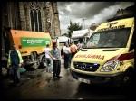 Een man in een gestreept T-shirt staat serieus te kijken van alle veegwagens en ambulances die passeren.
